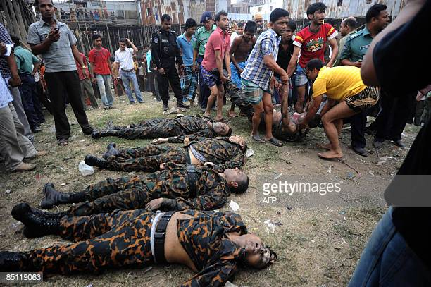Bangladeshis carry the body of an Bangladesh Rifles officer from the Buriganga river as four other bodies lie on the ground in Dhaka on February 26...