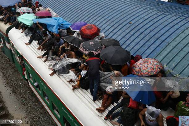Bangladeshis cover themselves fron the rain onto a train as they travel back home to meet their families ahead of the Muslim festival of Eid alFitr...