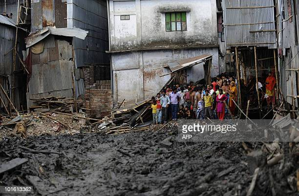 Bangladeshis look on after fire services ended the rescue operation at a fourstorey collapsed building in Dhaka on June 3 2010The death toll from the...