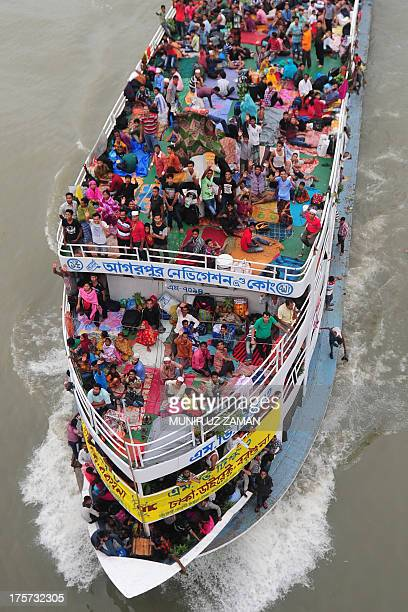 Bangladeshis ride a packed ferry as they rush home to be with their families in their respective villages ahead of the Eid alFitr festival at the...