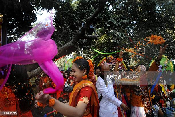 Bangladeshis throw marigold petals as they participate in a procession during the Boshonto Utshob festival in Dhaka on February 13 2010 The spring...