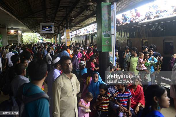 Bangladeshis wait to cram onto a train as they rush home to their respective villages to be with their families ahead of the Muslim festival of Eid...