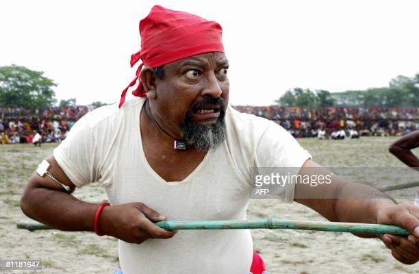 Bangladesh-media-agriculture-games,FEATURE by Helen Rowe A Bangladeshi farmer prepares to take part in a traditional stick fight during the...