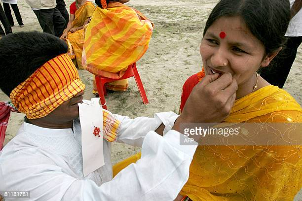 Bangladesh-media-agriculture-games,FEATURE by Helen Rowe A Bangladeshi woman laughs as her blindfolded husband applies her lipstick as part of the...
