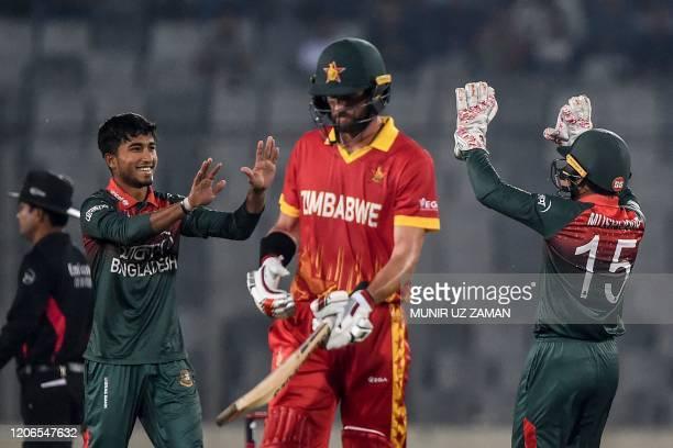 Bangladesh's Afif Hossain celebrates with teammate Mushfiqur Rahim after the dismissal of Zimbabwe's Craig Ervine during the second Twenty20...