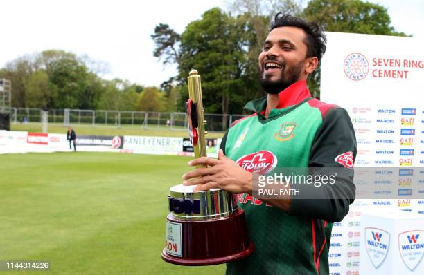 Bangladesh's captain Mashrafe Mortaza holds the winner's trophy after the oneday international TriNation Series final between Bangladesh and West...