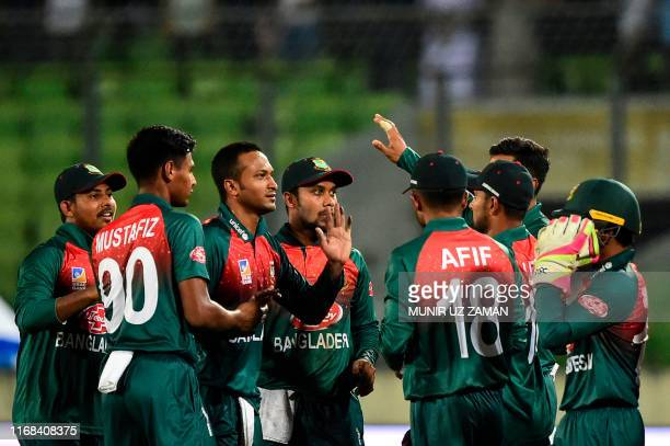 Bangladesh's captain Shakib Al Hasan celebrates with his teammates after the dismissal of Afghanistan's Hazratullah Zazai during the third match...