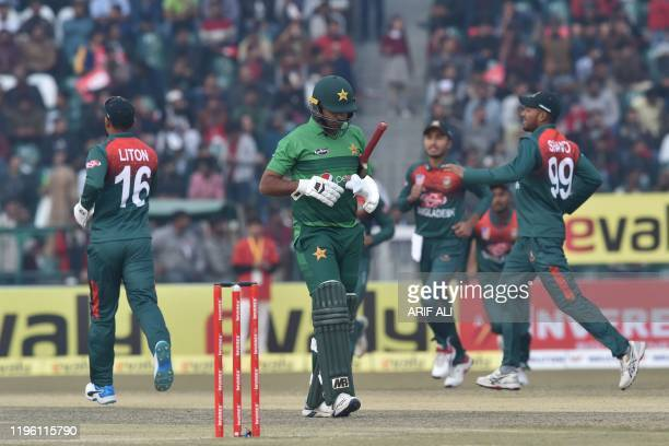 Bangladesh's cricketers celebrate the dismissal of Pakistan's Ahsan Ali as he walks back to the pavilion during the second T20 international cricket...