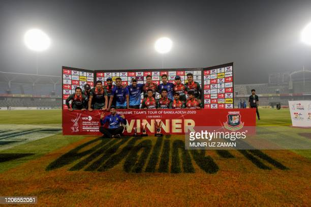 Bangladesh's cricketers pose for photographs with the trophy after winning the second Twenty20 international cricket match of a two-match series...