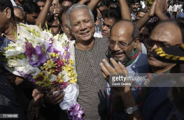 Bangladesh's first ever Nobel Peace Prize recipient Muhammad Yunus greets the crowd as he arrives at Grameen Bank on October 14 2006 in Dhaka...