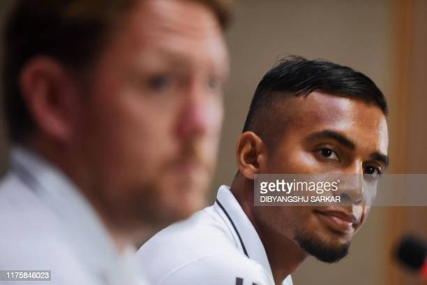Bangladesh's football captain Jamal Bhuyan looks on next to coach Jamie Day gestures during a press conference on the eve of their World Cup 2022...