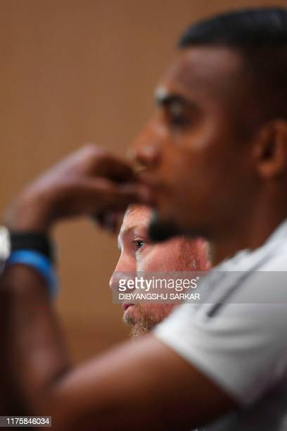 Bangladesh's football coach Jamie Day listens to a question next to Bangladeshi captain Jamal Bhuyan and gestures during a press conference on the...