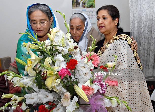 Bangladesh's former prime minister and Awami League chief Sheikh Hasina Wajed receives flowers from her sister Rehana and Khadina Hussain sister of...