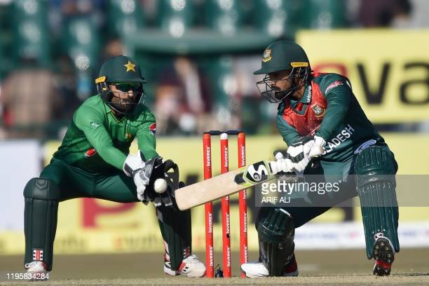 Bangladesh's Liton Das plays a shot as Pakistan's wicketkeeper Mohammad Rizwan looks on during the first T20 international cricket match of a...