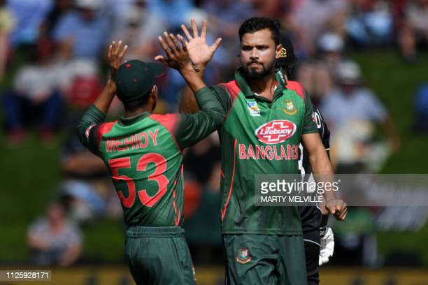 Bangladesh's Mashrafe Mortaza celebrates New Zealand's Colin Munro being caught with LBW with team mate Mehidy Hasan Miraz during the 3rd ODI cricket...