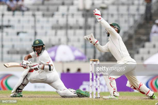 Bangladesh's Mehedi Hasan Miraz left plays a shot as Australia's wicketkeeper Matthew Wade attempts to catch the ball during the third day of their...