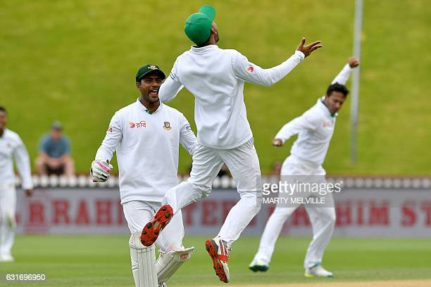 Bangladesh's Mehedi Hasan Siddique C celebrates catching New Zealand's Henry Nicholls with team mate Imrul Kayes during day four of the first...