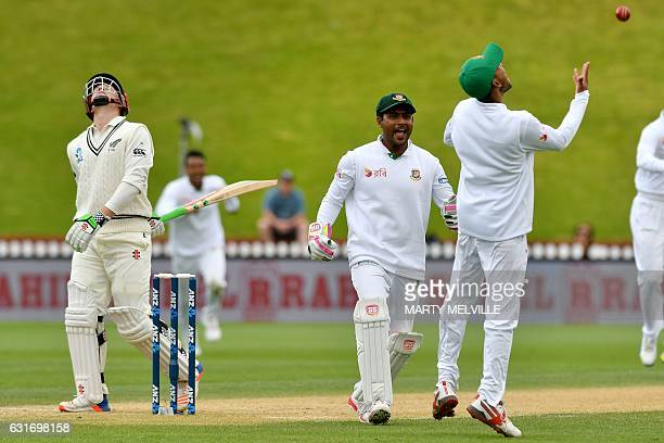 Bangladesh's Mehedi Hasan Siddique celebrates catching New Zealand's Henry Nicholls with team mate Imrul Kayes during day four of the first...