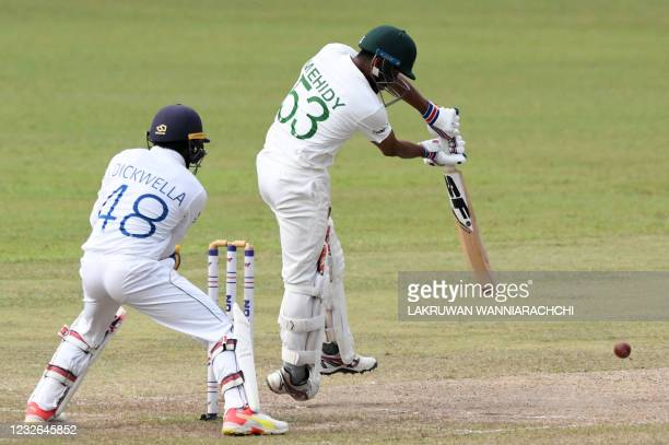 Bangladesh's Mehidy Hasan Miraz plays a shot as Sri Lanka's wicketkeeper Niroshan Dickwella watches during the fourth day of the second and final...