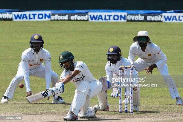 Bangladesh's Mehidy Hasan Miraz plays a shot as Sri Lanka's wicketkeeper Niroshan Dickwella looks on during the final day of the second and final...
