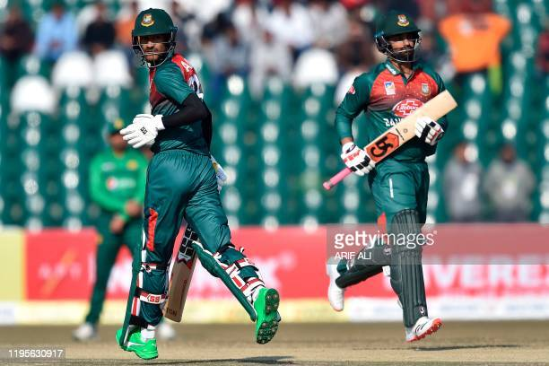 Bangladesh's Mohammad Naim and Tamim Iqbal run between the wickets during the first T20 international cricket match of a threematch series between...