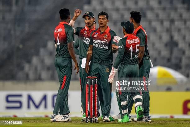 Bangladesh's Mohammad Saifuddin celebrates with teammates after the dismissal of Zimbabwe's Sikandar Raza during the second Twenty20 international...