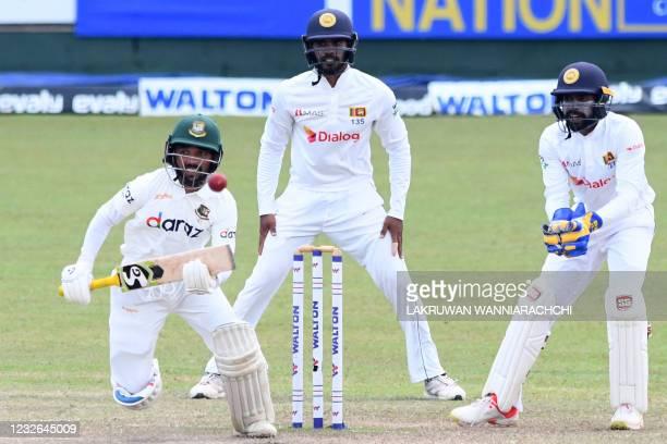 Bangladesh's Mominul Haque plays a shot as Sri Lanka's wicketkeeper Niroshan Dickwella and Dhananjaya de Silva watch during the fourth day of the...