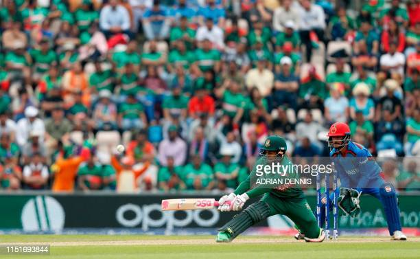 Bangladesh's Mushfiqur Rahim attempts a reverse sweep shot as Afghanistan's wicketkeeper Ikram Ali Khil looks on during the 2019 Cricket World Cup...