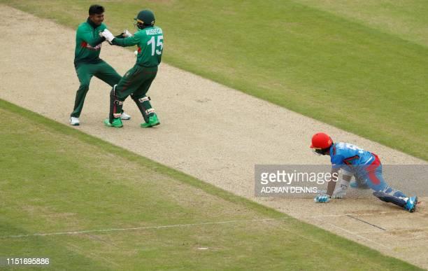 Bangladesh's Mushfiqur Rahim celebrates with teammate Mosaddek Hossain after stumping Afghanistan's Hashmatullah Shahidi during the 2019 Cricket...