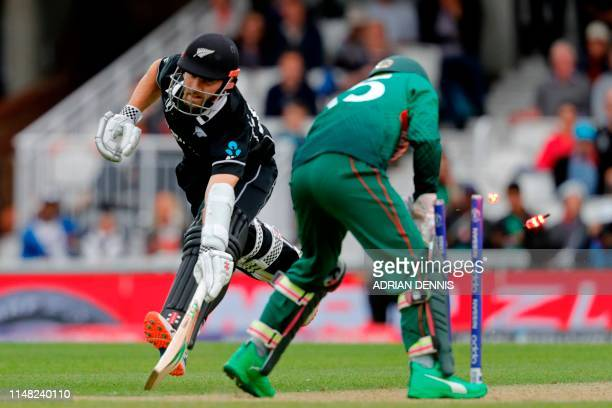 TOPSHOT Bangladesh's Mushfiqur Rahim knocks the bails off before gathering the ball meaning New Zealand's captain Kane Williamson avoids being run...
