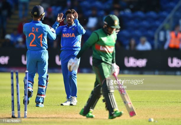 Bangladesh's Mushfiqur Rahim leaves the crease as India's Kuldeep Yadav celebrates his wicket for 90 during the 2019 Cricket World Cup warm up match...
