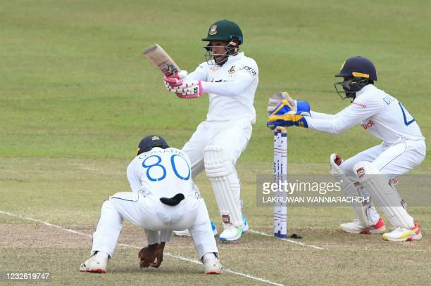Bangladesh's Mushfiqur Rahim plays a shot as Sri Lanka's wicketkeeper Niroshan Dickwella looks on during the third day of the second and final Test...