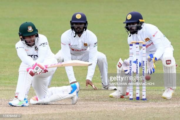 Bangladesh's Mushfiqur Rahim plays a shot as Sri Lanka's wicketkeeper Niroshan Dickwella and Dhananjaya de Silva watch during the fourth day of the...