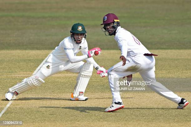 Bangladesh's Mushfiqur Rahim plays a shot as West Indies Nkrumah Bonner watches during the first day of the first cricket Test match between...
