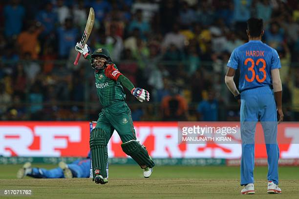 Bangladesh's Mushfiqur Rahimgestures after scoring a boundary as Indian bowler Hardik Pandaylooks on during the World T20 cricket tournament match...