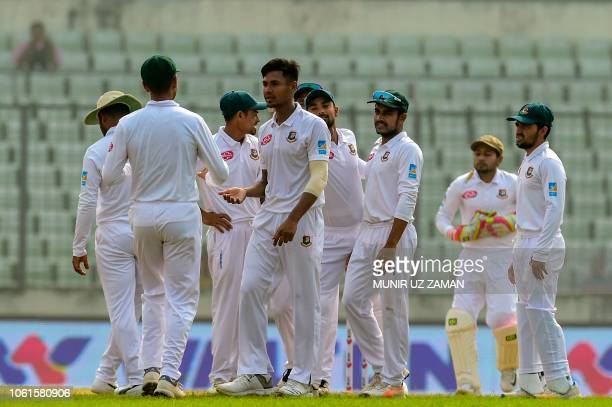 Bangladesh's Mustafizur Rahman celebrates with teammates after the dismissal of Zimbabwe batsman Sean Williams during the fifth day of the second...