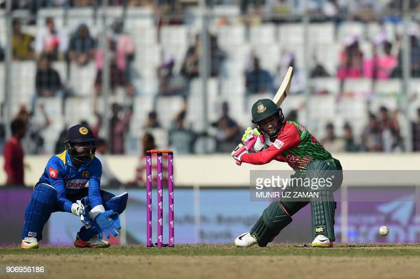 Bangladesh's Mustafizur Rahman plays a shot as Sri Lanka's Niroshan Dickwella looks on during the third one day international cricket match in the...