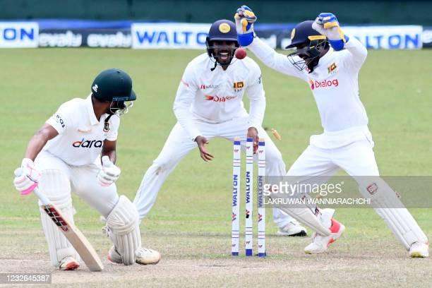 Bangladesh's Najmul Hossain Shanto is clean bowled as Sri Lanka's wicketkeeper Niroshan Dickwella and Dhananjaya de Silva watch during the fourth day...