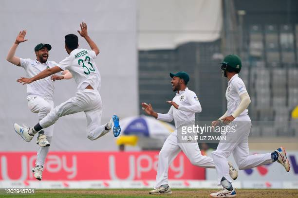 Bangladesh's Nayeem Hasan celebrates with teammates Ebadot Hossain after the dismissal of the Zimbabwe's Donald Tiripano during the third day of a...