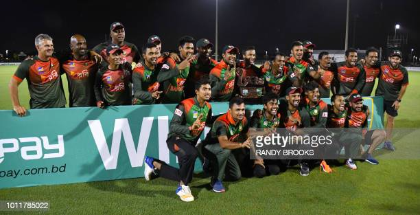 Bangladesh's players pose with the trophy after winning the 3rd and final T20i match against West Indies at Central Broward Regional Park Stadium in...