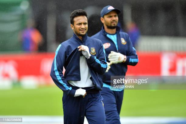 Bangladesh's players Shakib Al Hasan and captain Mashrafe Mortaza walk off the field as rain halts a training session at The County Ground in Taunton...