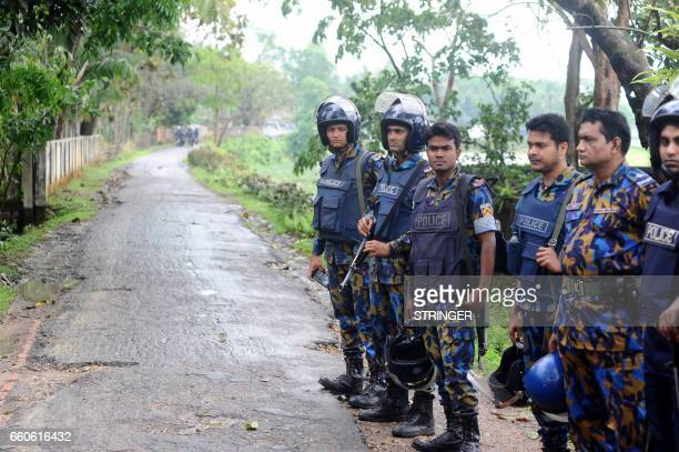 Bangladesh's policemen stand guard on a road during an operation to storm an Islamist extremist hideout in the town of Moulvibazar on March 30 2017...