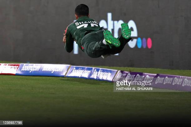 Bangladesh's Shakib Al Hasan dives over the boundary line to catch the ball during the ICC mens Twenty20 World Cup cricket match between Bangladesh...