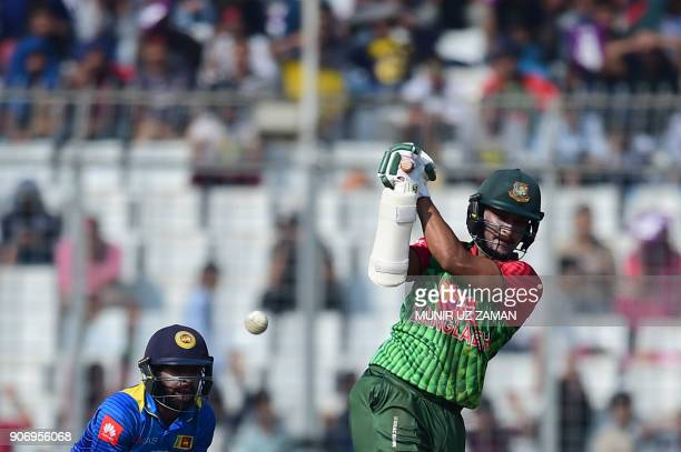 Bangladesh's Shakib Al Hasan plays a shot as Sri Lanka's Niroshan Dickwella looks on during the third one day international cricket match in the...