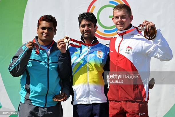 Bangladesh's silver medalist Abdullah Baki India's gold medalist Abhinav Bindra and England's bronze medalist Daniel Rivers celebrate with their...