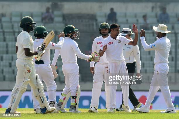 Bangladesh's Taijul Islam celebrates with teammates after the dismissal of Zimbabwe's Donald Tiripano during the third day of the second Test cricket...