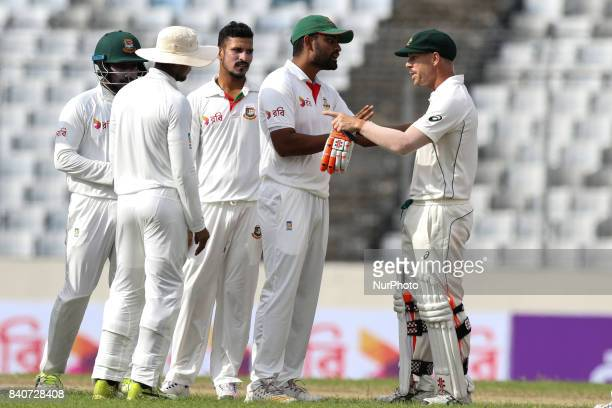 Bangladesh's Tamim Iqbal center tries to break an argument between Australia's David Warner right and Bangladesh's Sabbir Rahman during day three of...