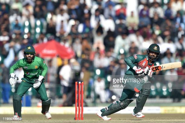 Bangladesh's Tamim Iqbal plays a shot as Pakistan's wicketkeeper Mohammad Rizwan looks on during the first T20 international cricket match of a...