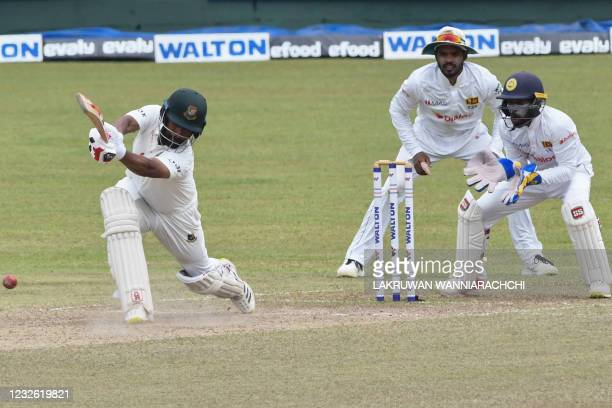 Bangladesh's Tamim Iqbal plays a shot as Sri Lanka's wicketkeeper Niroshan Dickwella and Dhananjaya de Silva look on during the third day of the...