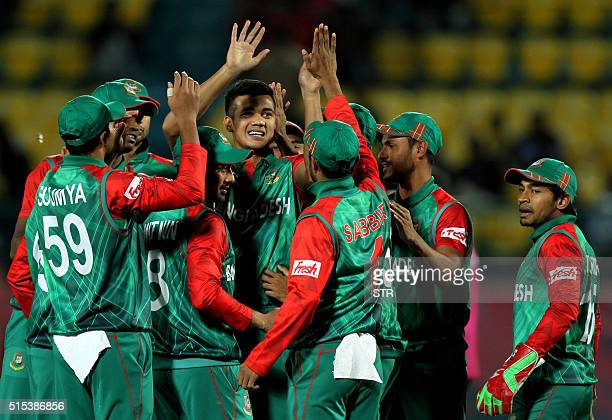 Bangladesh's Taskin Ahmed is surrounded by teammates after taking the wicket of Oman's Zeeshan Maqsood during the qualifying match for the World T20...